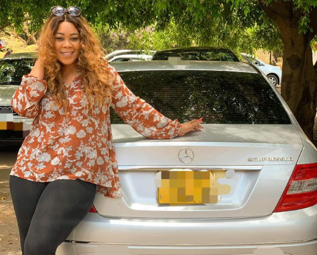 Madam Boss with new vehicle she got from Passion Java. Passion Java buys Madam boss a new car